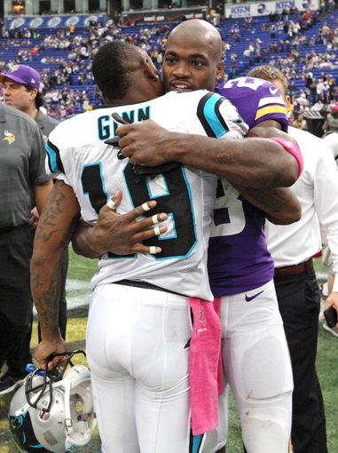 Oct 13, 2013; Minneapolis, MN, USA; Minnesota Vikings running back Adrian Peterson (28) is hugged by Carolina Panthers wide receiver Ted Ginn (19) following the game at Mall of America Field at H.H.H. Metrodome. The Panthers defeated the Vikings 35-10. Mandatory Credit: Brace Hemmelgarn-USA TODAY Sports