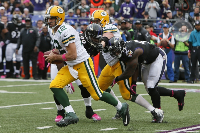 Oct 13, 2013; Baltimore, MD, USA; Green Bay Packers quarterback Aaron Rodgers (12) is pressured by Baltimore Ravens linebacker Pernell McPhee (90) and linebacker Terrell Suggs (55) at M&T Bank Stadium. Mandatory Credit: Mitch Stringer-USA TODAY Sports