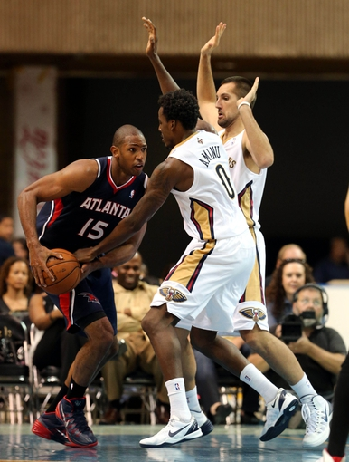 Oct 13, 2013; Biloxi, MS, USA; Atlanta Hawks power forward Al Horford (15) is double teamed by New Orleans Pelicans forwards Al-Farouq Aminu (0) and Ryan Anderson (33) during the second half of their game at the Mississippi Coast Coliseum. The Pelicans won 105-73. Mandatory Credit: Chuck Cook-USA TODAY Sports