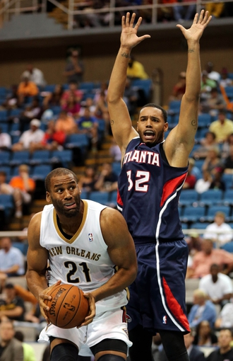 Oct 13, 2013; Biloxi, MS, USA; New Orleans Pelicans power forward Arinze Onuaku (21) looks to shoot around Atlanta Hawks power forward Mike Scott (32) during the second half of their game at the Mississippi Coast Coliseum. The Pelicans won 105-73. Mandatory Credit: Chuck Cook-USA TODAY Sports