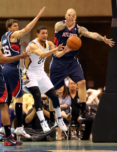 Oct 13, 2013; Biloxi, MS, USA; New Orleans Pelicans shooting guard Austin Rivers (25) is defended by Atlanta Hawks shooting guard Kyle Korver (26) and power forward Pero Antic (6) during the first half of their game at the Mississippi Coast Coliseum. Mandatory Credit: Chuck Cook-USA TODAY Sports