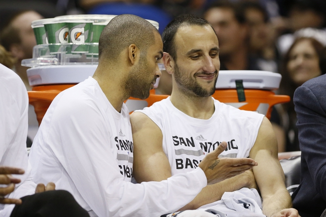 Oct 13, 2013; San Antonio, TX, USA; San Antonio Spurs guard Tony Parker (left) talks to Manu Ginobili (right) during the second half against the Phoenix Suns at AT&T Center. The Suns won 106-99. Mandatory Credit: Soobum Im-USA TODAY Sports