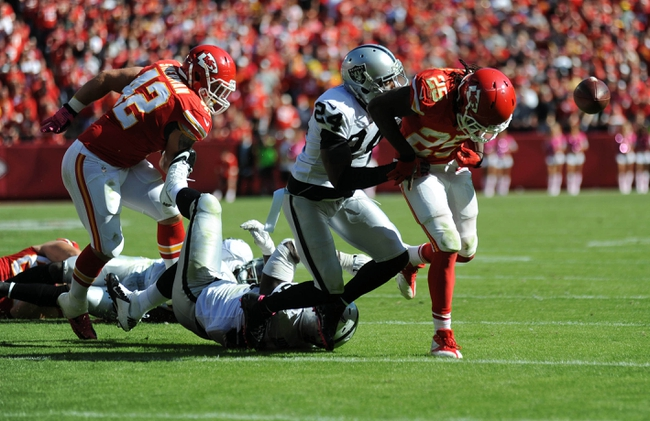 Oct 13, 2013; Kansas City, MO, USA; Oakland Raiders free safety Charles Woodson (24) causes  Kansas City Chiefs running back Jamaal Charles (25) to lose the ball during the second half at Arrowhead Stadium. The Chiefs won 24-7. Mandatory Credit: Denny Medley-USA TODAY Sports