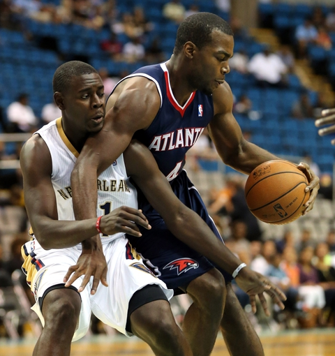 Oct 13, 2013; Biloxi, MS, USA; New Orleans Pelicans point guard Jrue Holiday (11) fouls Atlanta Hawks power forward Paul Millsap (4) during the first half of their game at the Mississippi Coast Coliseum. Mandatory Credit: Chuck Cook-USA TODAY Sports