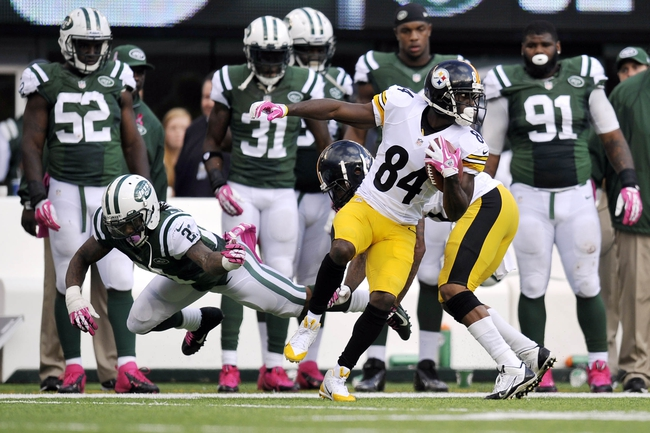 Oct 13, 2013; East Rutherford, NJ, USA; Pittsburgh Steelers wide receiver Antonio Brown (84) eludes the tackle of New York Jets defensive back Ellis Lankster (21) after making a catch during the second half at MetLife Stadium. The Steelers won the game 19-6. Mandatory Credit: Joe Camporeale-USA TODAY Sports