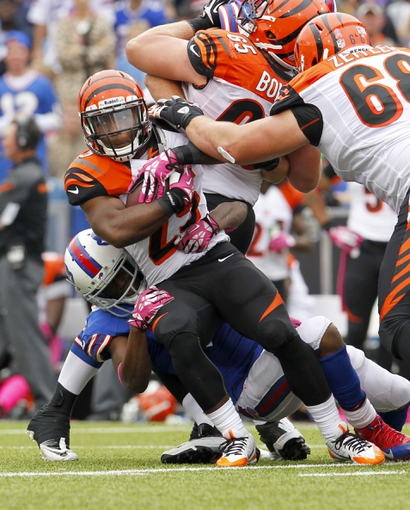 Oct 13, 2013; Orchard Park, NY, USA; Cincinnati Bengals running back Giovani Bernard (25) gets tackled by Buffalo Bills cornerback Leodis McKelvin (21) during the second half at Ralph Wilson Stadium. Bengals beat the Bills 27 to 24 in overtime.  Mandatory Credit: Timothy T. Ludwig-USA TODAY Sports