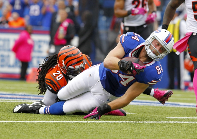 Oct 13, 2013; Orchard Park, NY, USA; Cincinnati Bengals free safety Reggie Nelson (20) tackles Buffalo Bills tight end Scott Chandler (84) after a catch during the second half at Ralph Wilson Stadium. Bengals beat the Bills 27 to 24 in overtime.  Mandatory Credit: Timothy T. Ludwig-USA TODAY Sports