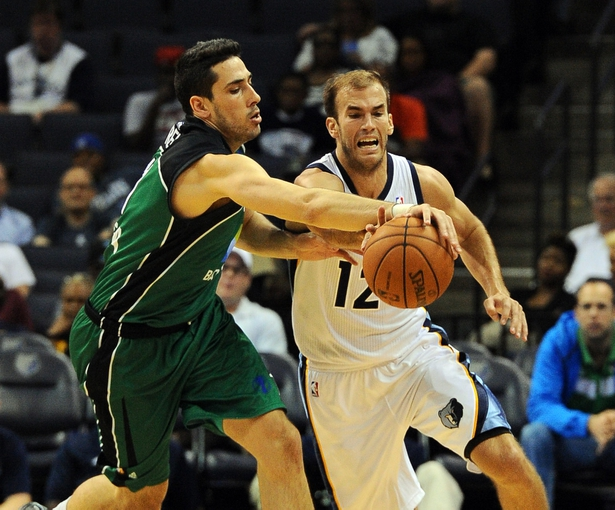 Oct 13, 2013; Memphis, TN, USA; Memphis Grizzlies shooting guard Nick Calathes (12) and Haifa forward Ben Reis (11) fight for the ball during the second quarter  at FedExForum. Mandatory Credit: Justin Ford-USA TODAY Sports