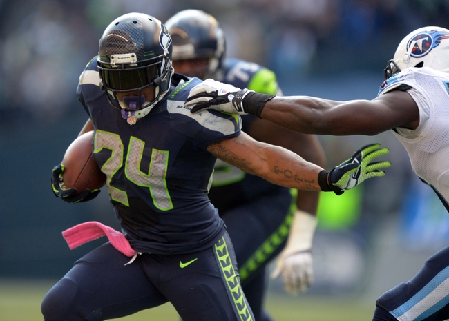 Oct 13, 2013; Seattle, WA, USA; Seattle Seahawks running back Marshawn Lynch (24) is pursued by Tennessee Titans linebacker Moise Fokou (53) at CenturyLink Field. The Seahawks defeated the Titans 20-13. Mandatory Credit: Kirby Lee-USA TODAY Sports
