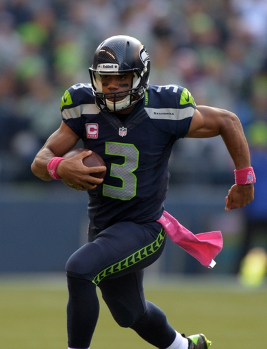 Oct 13, 2013; Seattle, WA, USA; Seattle Seahawks quarterback Russell Wilson (3) scrambles against the Tennessee Titans at CenturyLink Field. The Seahawks defeated the Titans 20-13. Mandatory Credit: Kirby Lee-USA TODAY Sports