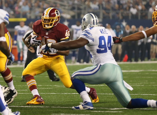 Oct 13, 2013; Arlington, TX, USA; Washington Redskins running back Alfred Morris (46) runs with the ball against Dallas Cowboys defensive end DeMarcus Ware (94) at AT&T Stadium. Mandatory Credit: Matthew Emmons-USA TODAY Sports