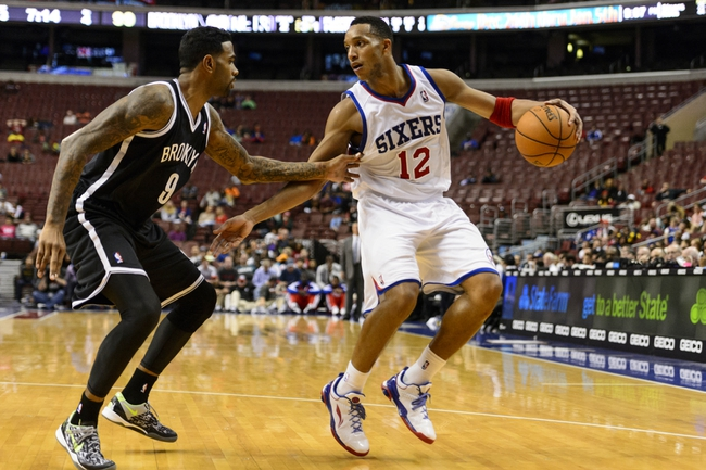 Oct 14, 2013; Philadelphia, PA, USA; Philadelphia 76ers guard Evan Turner (12) is defended by Brooklyn Nets forward Gary Forbes (9) during the fourth quarter at Wells Fargo Center. The Nets defeated the Sixers 127-97. Mandatory Credit: Howard Smith-USA TODAY Sports