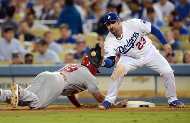 October 14, 2013; Los Angeles, CA, USA; St. Louis Cardinals center fielder Jon Jay (19) slides back to first against the tag of Los Angeles Dodgers first baseman Adrian Gonzalez (23) in the eighth inning in game three of the National League Championship Series baseball game at Dodger Stadium. Mandatory Credit: Jayne Kamin-Oncea-USA TODAY Sports
