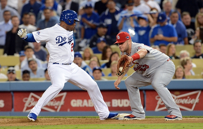 October 14, 2013; Los Angeles, CA, USA; Los Angeles Dodgers left fielder Carl Crawford (25) goes back to first against the tag of St. Louis Cardinals first baseman Matt Adams (53) in the eighth inning in game three of the National League Championship Series baseball game at Dodger Stadium. Mandatory Credit: Jayne Kamin-Oncea-USA TODAY Sports