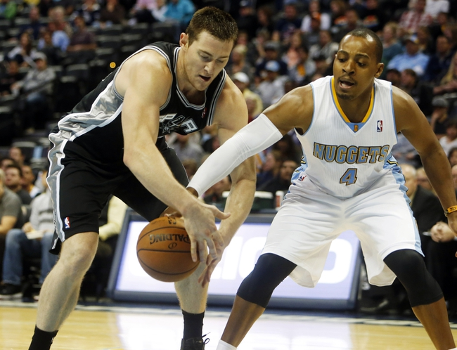 Oct 14, 2013; Denver, CO, USA; San Antonio Spurs forward Aron Baynes (16) battles Denver Nuggets guard Randy Foye (4) for the ball during the second half at Pepsi Center. The Nuggets won 98-94. Mandatory Credit: Chris Humphreys-USA TODAY Sports