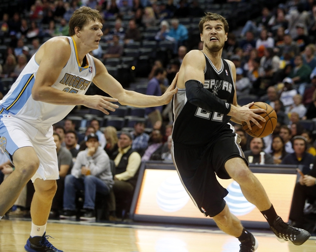Oct 14, 2013; Denver, CO, USA; San Antonio Spurs forward Tiago Splitter (22) drives to the basket against Denver Nuggets center Timofey Mozgov (25) during the second half at Pepsi Center. The Nuggets won 98-94. Mandatory Credit: Chris Humphreys-USA TODAY Sports