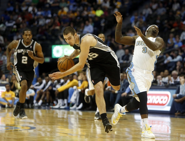 Oct 14, 2013; Denver, CO, USA; San Antonio Spurs guard Nando De Colo (25) is fouled by Denver Nuggets guard Ty Lawson (3) during the second half at Pepsi Center. The Nuggets won 98-94. Mandatory Credit: Chris Humphreys-USA TODAY Sports