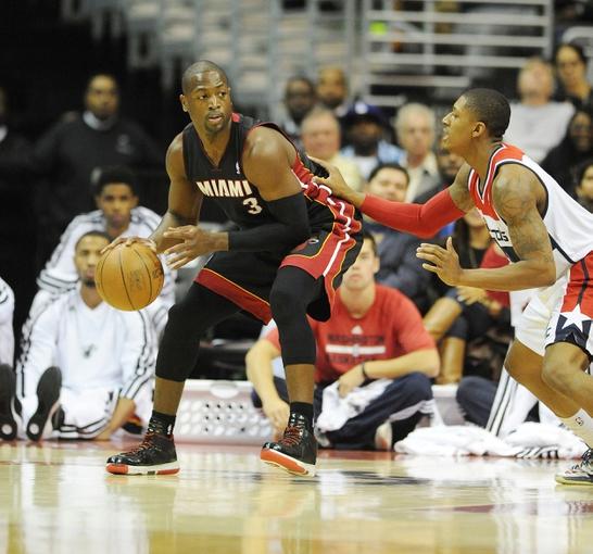 Oct 15, 2013; Washington, DC, USA; Miami Heat guard Dwyane Wade (3) dribbles the ball as Washington Wizards shooting guard Bradley Beal (3) defends during the first half at the Verizon Center. Mandatory Credit: Brad Mills-USA TODAY Sports