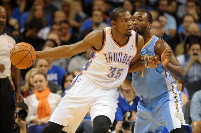 Oct 15, 2013; Oklahoma City, OK, USA; Oklahoma City Thunder small forward Kevin Durant (35) handles the ball against Denver Nuggets shooting guard Jordan Hamilton (1) during the second quarter at Chesapeake Energy Arena. Mandatory Credit: Mark D. Smith-USA TODAY Sports