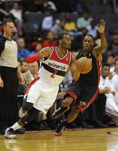 Oct 15, 2013; Washington, DC, USA; Washington Wizards point guard John Wall (2) dribbles the ball as Miami Heat point guard Mario Chalmers (15) defends during the second half at the Verizon Center. Mandatory Credit: Brad Mills-USA TODAY Sports