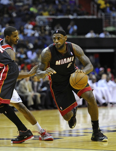 Oct 15, 2013; Washington, DC, USA; Miami Heat small forward LeBron James (6) dribbles the ball past Washington Wizards small forward Trevor Ariza (1) during the second half at the Verizon Center. Mandatory Credit: Brad Mills-USA TODAY Sports