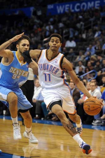 Oct 15, 2013; Oklahoma City, OK, USA; Oklahoma City Thunder shooting guard Jeremy Lamb (11) drives to the hoop against Denver Nuggets shooting guard Evan Fournier (94) during the third quarter at Chesapeake Energy Arena. Mandatory Credit: Mark D. Smith-USA TODAY Sports