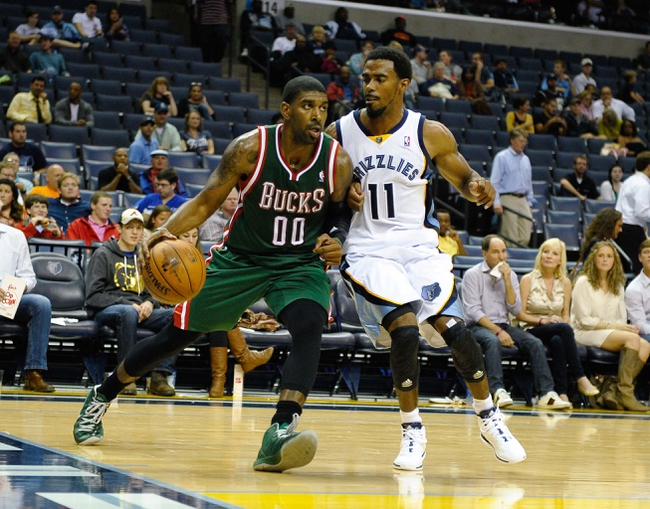 Oct 15, 2013; Memphis, TN, USA; Milwaukee Bucks shooting guard O.J. Mayo (00) drives to the basket against Memphis Grizzlies point guard Mike Conley (11) during the third quarter at FedExForum. Memphis Grizzlies defeat Milwaukee Bucks 102 - 99 Mandatory Credit: Justin Ford-USA TODAY Sports