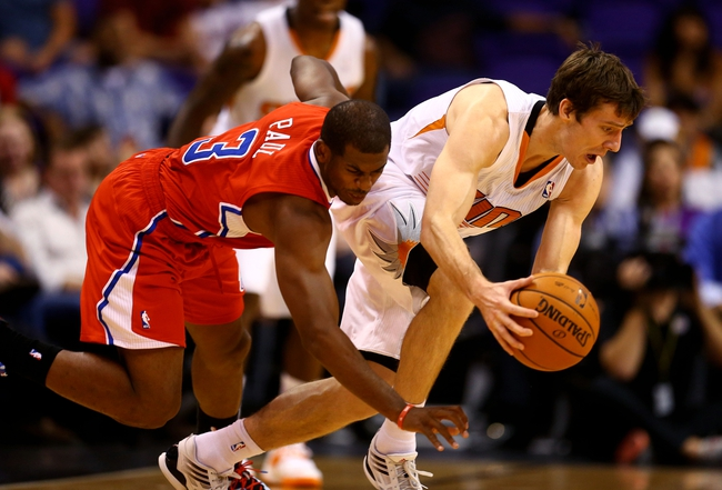 Oct 15, 2013; Phoenix, AZ, USA; Los Angeles Clippers guard Chris Paul (left) battles for a loose ball against Phoenix Suns guard Goran Dragic at US Airways Center. Mandatory Credit: Mark J. Rebilas-USA TODAY Sports