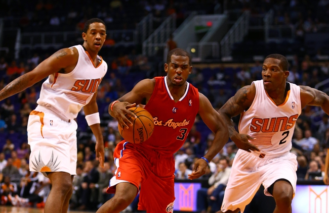 Oct 15, 2013; Phoenix, AZ, USA; Los Angeles Clippers guard Chris Paul (center) controls the ball against Phoenix Suns center Channing Frye (left) and guard Eric Bledsoe at US Airways Center. Mandatory Credit: Mark J. Rebilas-USA TODAY Sports