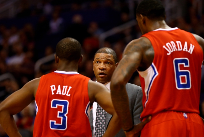 Oct 15, 2013; Phoenix, AZ, USA; Los Angeles Clippers head coach Doc Rivers (center) talks with guard Chris Paul (3) and center DeAndre Jordan against the Phoenix Suns at US Airways Center. Mandatory Credit: Mark J. Rebilas-USA TODAY Sports