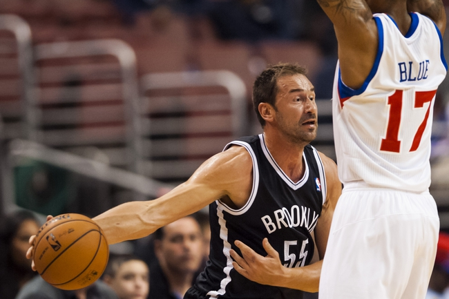 Oct 14, 2013; Philadelphia, PA, USA; Brooklyn Nets guard Marko Jaric (55) passes the ball around the defense of Philadelphia 76ers guard Vander Blue (17) during the fourth quarter at Wells Fargo Center. The Nets defeated the Sixers 127-97. Mandatory Credit: Howard Smith-USA TODAY Sports