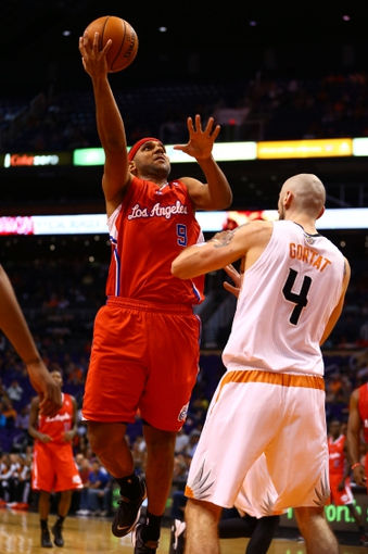 Oct 15, 2013; Phoenix, AZ, USA; Los Angeles Clippers forward Jared Dudley (left) drives to the basket against Phoenix Suns center Marcin Gortat at US Airways Center. Mandatory Credit: Mark J. Rebilas-USA TODAY Sports