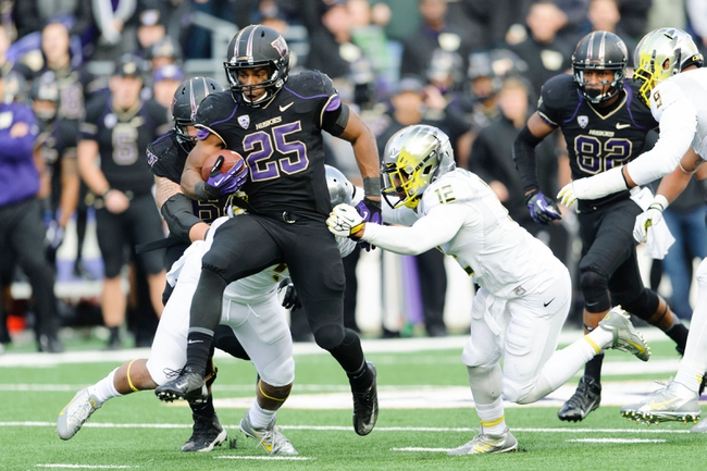 Oct 12, 2013; Seattle, WA, USA; Washington Huskies running back Bishop Sankey (25) breaks a tackle by Oregon Ducks defensive back Brian Jackson (12) during the game at Husky Stadium. Oregon defeated Washington 45-24. Mandatory Credit: Steven Bisig-USA TODAY Sports
