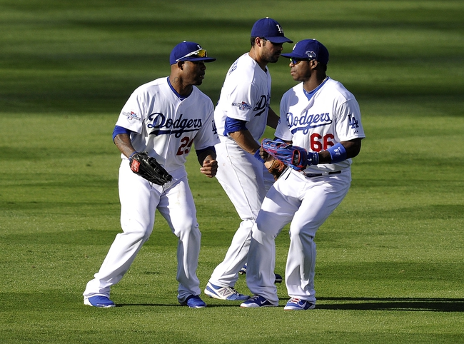 October 16, 2013; Los Angeles, CA, USA; Los Angeles Dodgers left fielder Carl Crawford (25), right fielder Yasiel Puig (66) and center fielder Andre Ethier (16) celebrate the 6-4 victory against the St. Louis Cardinals in game five of the National League Championship Series baseball game at Dodger Stadium. Mandatory Credit: Robert Hanashiro-USA TODAY Sports