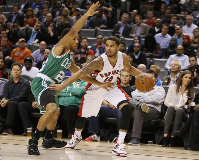 Oct 16, 2013; Toronto, Ontario, CAN; Toronto Raptors guard D.J. Augustin (14) dribbles the ball against Boston Celtics guard Phil Pressey (26) during the first half at Air Canada Centre. Mandatory Credit: John E. Sokolowski-USA TODAY Sports