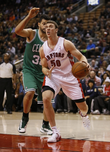 Oct 16, 2013; Toronto, Ontario, CAN; Toronto Raptors forward Tyler Hansbrough (50) drives to the basket against Boston Celtics center Vitor Faverani (left) during the first half at Air Canada Centre. Mandatory Credit: John E. Sokolowski-USA TODAY Sports