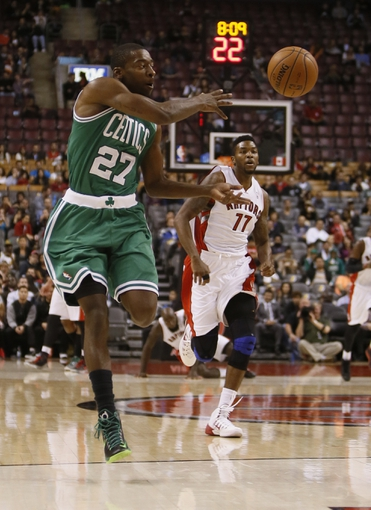Oct 16, 2013; Toronto, Ontario, CAN; Boston Celtics guard Jordan Crawford (27) passes the ball as Toronto Raptors guard Julyan Stone (77) chases during the second half at Air Canada Centre. Toronto defeated Boston 99-97. Mandatory Credit: John E. Sokolowski-USA TODAY Sports
