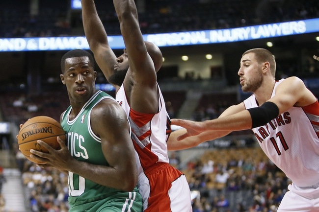 Oct 16, 2013; Toronto, Ontario, CAN; Toronto Raptors forward Quincy Acy (center) and center Jonas Valanciunas (17) defend against Boston Celtics forward Brandon Bass (30) during the second half at Air Canada Centre. Toronto defeated Boston 99-97. Mandatory Credit: John E. Sokolowski-USA TODAY Sports