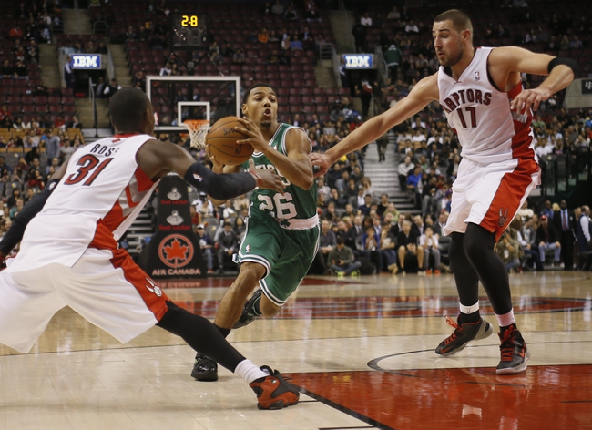 Oct 16, 2013; Toronto, Ontario, CAN; Boston Celtics guard Phil Pressey (26) dribbles between Toronto Raptors guard Terrence Ross (31) and center Jonas Valanciunas (17) during the second half at Air Canada Centre. Toronto defeated Boston 99-97. Mandatory Credit: John E. Sokolowski-USA TODAY Sports