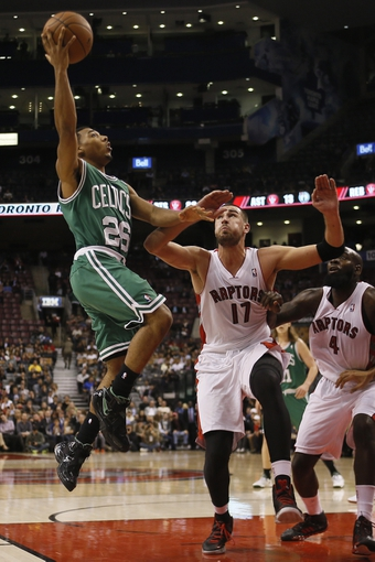 Oct 16, 2013; Toronto, Ontario, CAN; Boston Celtics guard Phil Pressey (26) goes up for a basket as Toronto Raptors center Jonas Valanciunas (17) and forward Quincy Acy (4) look on during the second half at Air Canada Centre. Toronto defeated Boston 99-97. Mandatory Credit: John E. Sokolowski-USA TODAY Sports