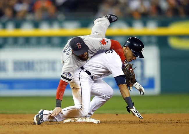 Oct 16, 2013; Detroit, MI, USA; Boston Red Sox second baseman Dustin Pedroia (15) collides with Detroit Tigers shortstop Jose Iglesias (1) as he turns a double play during the sixth inning in game four of the American League Championship Series baseball game at Comerica Park. Mandatory Credit: Rick Osentoski-USA TODAY Sports