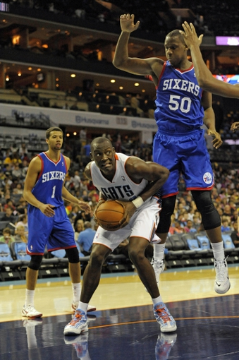 Oct 17, 2013; Charlotte, NC, USA; Charlotte Bobcats forward Bismack Biyombo (0) looks to shoot as he is defended by Philadelphia 76ers guard Michael Carter-Williams (1) and forward guard Lavoy Allen (50) during the pre season game at Time Warner Cable Arena. Bobcats win 110-84. Mandatory Credit: Sam Sharpe-USA TODAY Sports