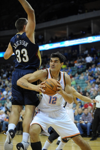 Oct 17, 2013; Tulsa, OK, USA; Oklahoma City Thunder center Steven Adams (12) drives to the basket against New Orleans Pelicans power forward Ryan Anderson (33) during the second quarter at BOK Center. Mandatory Credit: Mark D. Smith-USA TODAY Sports