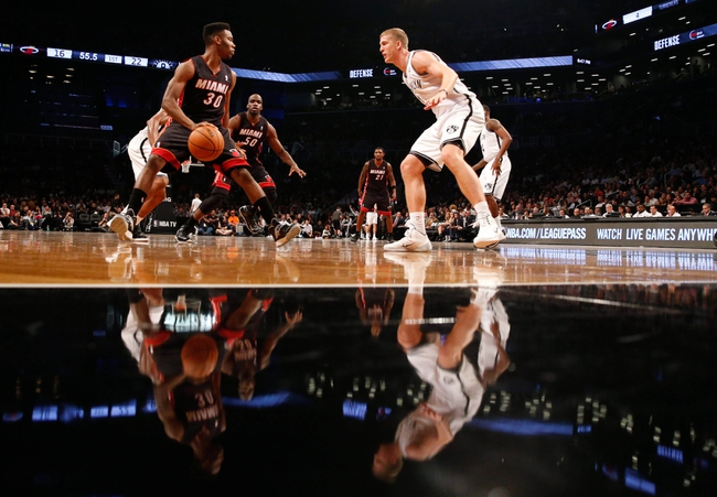 Oct 17, 2013; Brooklyn, NY, USA;  Miami Heat point guard Norris Cole (30) looks to drive around Brooklyn Nets power forward Mason Plumlee (1) during the first quarter at Barclays Center. Mandatory Credit: Anthony Gruppuso-USA TODAY Sports