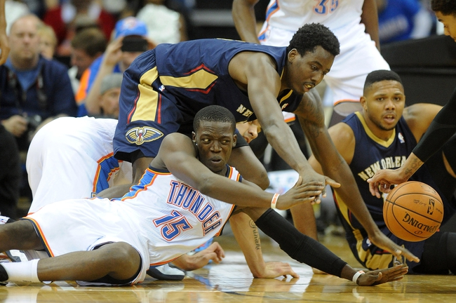 Oct 17, 2013; Tulsa, OK, USA; Oklahoma City Thunder point guard Reggie Jackson (15) fights for a loose ball with New Orleans Pelicans small forward Al-Farouq Aminu (0) during the second quarter at BOK Center. Mandatory Credit: Mark D. Smith-USA TODAY Sports