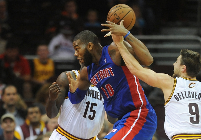 Oct 17, 2013; Cleveland, OH, USA; Cleveland Cavaliers shooting guard Matthew Dellavedova (9) fouls Detroit Pistons center Greg Monroe (10) as he drives to the basket during the game at Quicken Loans Arena. Mandatory Credit: Eric P. Mull-USA TODAY Sports