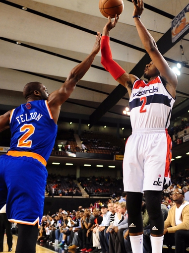 Oct 17, 2013; Baltimore, MD, USA; Washington Wizards guard John Wall (right) shoots the ball over New York Knicks guard Raymond Felton (left) at Baltimore Arena. Mandatory Credit: Evan Habeeb-USA TODAY Sports