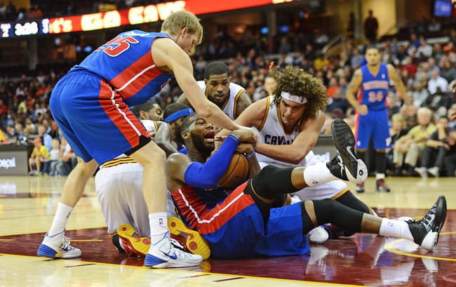 Oct 17, 2013; Cleveland, OH, USA; Cleveland Cavaliers power forward Anderson Varejao (17) and Detroit Pistons center Greg Monroe (10) battle for a loose ball during the game at Quicken Loans Arena. Mandatory Credit: Eric P. Mull-USA TODAY Sports