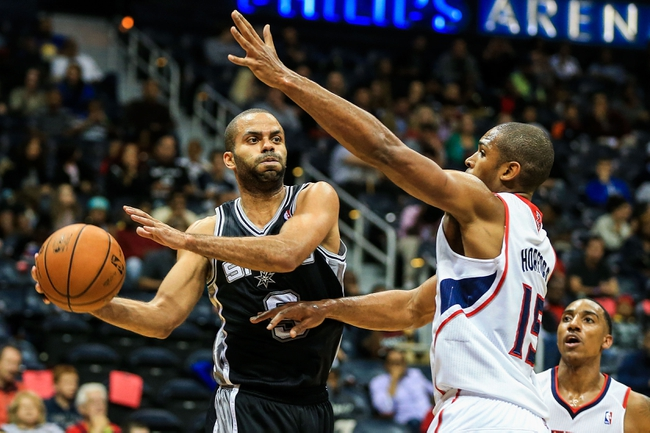 Oct 17, 2013; Atlanta, GA, USA; San Antonio Spurs point guard Tony Parker (9) passes the ball around Atlanta Hawks power forward Al Horford (15) in the second half at Philips Arena. The Spurs won 106-104. Mandatory Credit: Daniel Shirey-USA TODAY Sports
