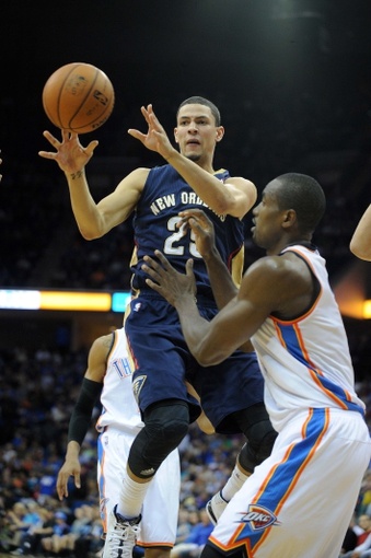 Oct 17, 2013; Tulsa, OK, USA; New Orleans Pelicans shooting guard Austin Rivers (25) passes the ball while defended by Oklahoma City Thunder power forward Serge Ibaka (9) during the third quarter at BOK Center. Mandatory Credit: Mark D. Smith-USA TODAY Sports